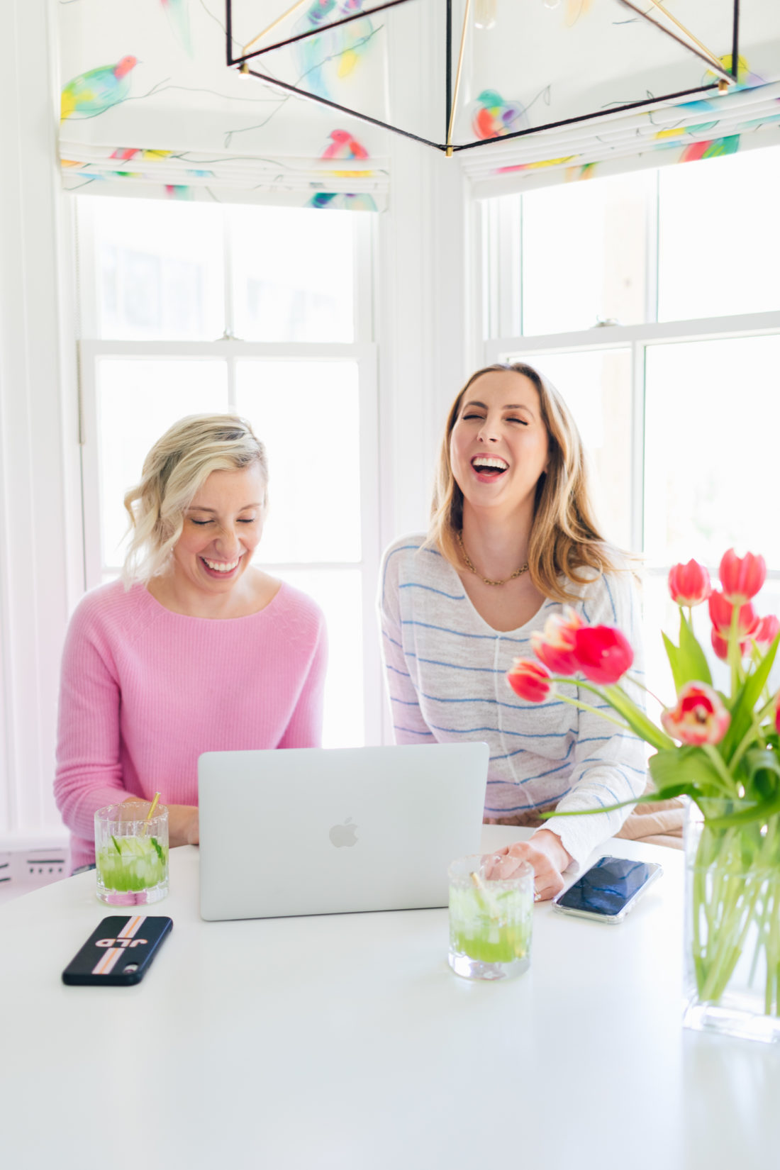 Eva Amurri Martino of Happily Eva After and Julia Dzafic of Lemon Stripes sit at a computer drinking margaritas and reminiscing on their parenting style