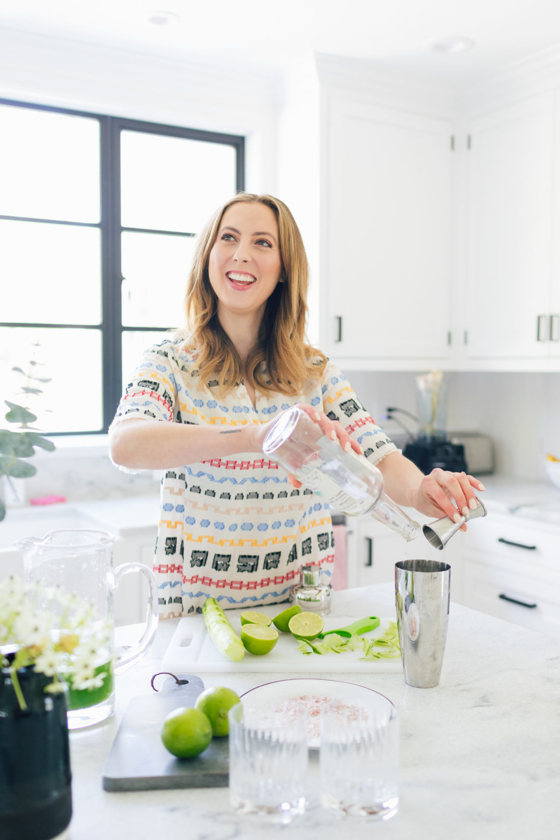 Eva Amurri Martino of Happily Eva After pour tequila into a cocktail shaker for cucumber margaritas