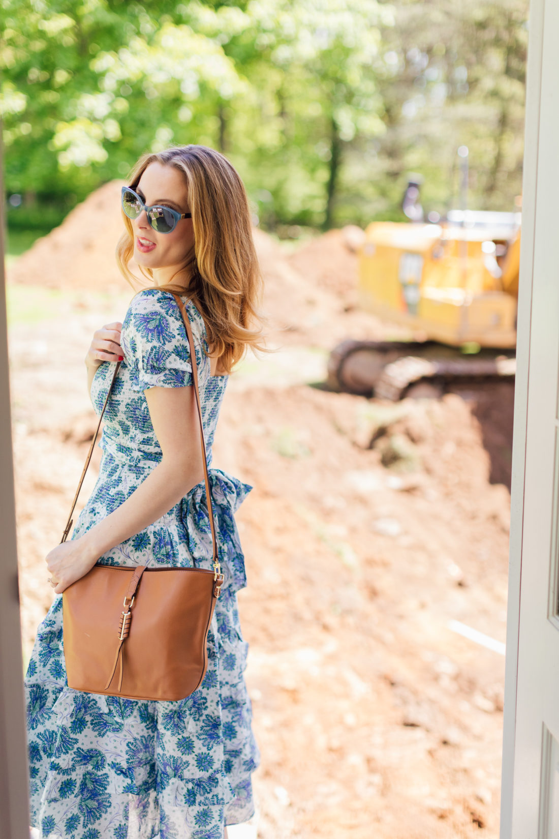 Eva Amurri Martino carries a btown leather bag on her shoulder next to her renovated home