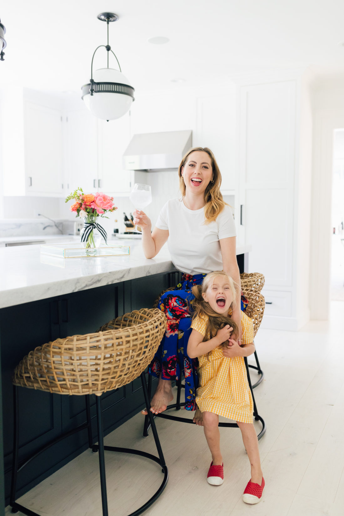 Eva Amurri Martino wears a crisp white t-shirt and a colorful skirt with her daughter Marlowe in her kitchen in Connecticut