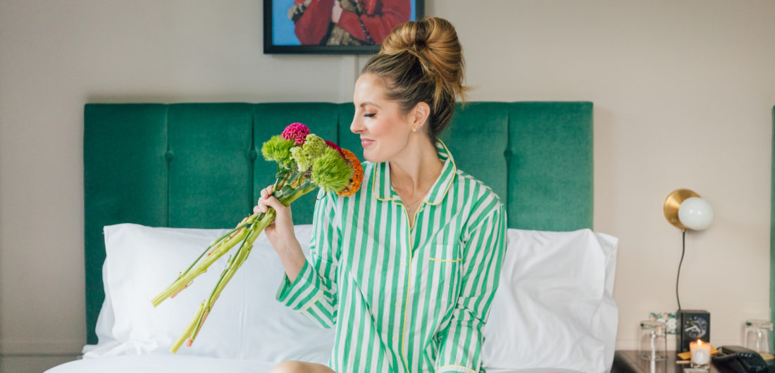 Eva Amurri Martino sits on a bed in a pair of green striped JCrew pajamas holding a bouquet of flowers