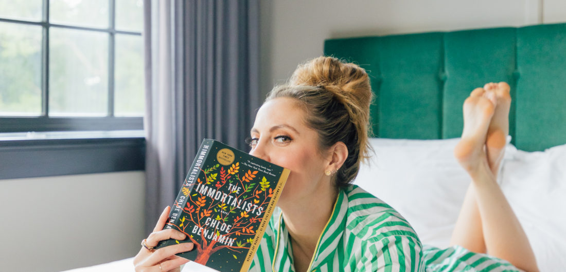 Eva Amurri Martino lays in bed reading her newest book club pick: The Immortalists by Chloe Benjamin