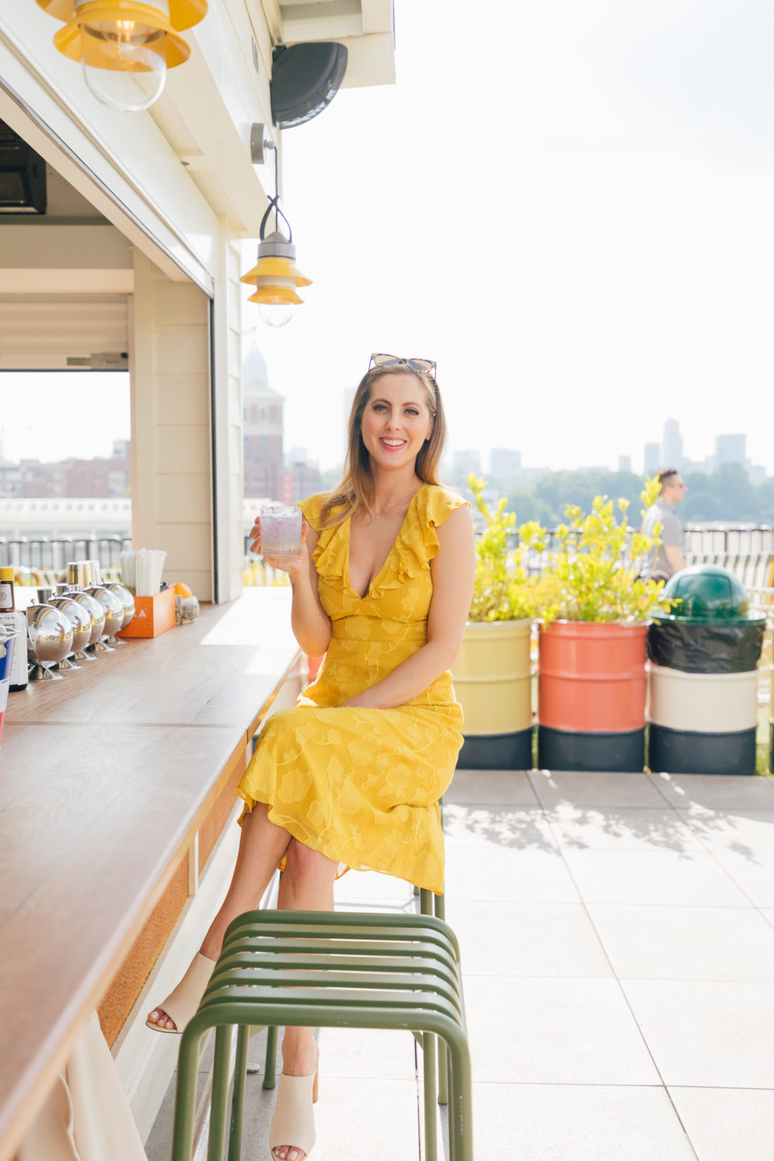 Eva Amurri Martino wears a bright yellow sress and sips on a cocktail at an outdoor bar