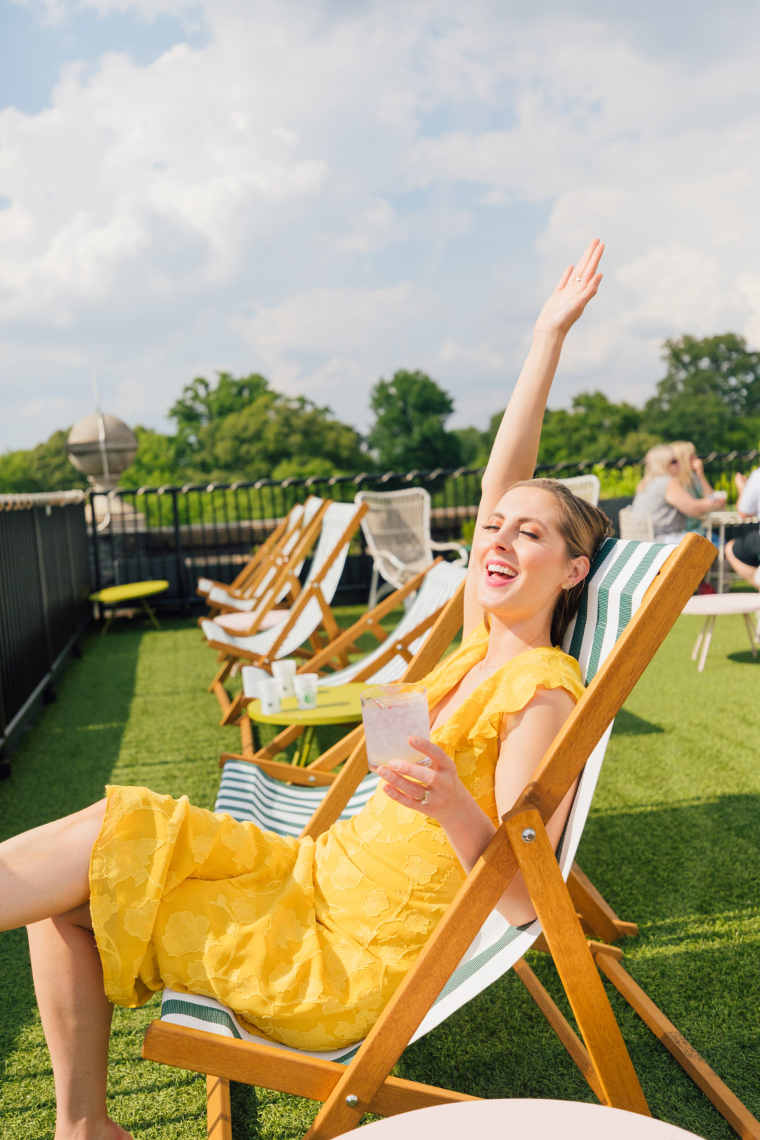 Eva Amurri Martino sips on a cocktail and lounges on a chair at a rooftop bar