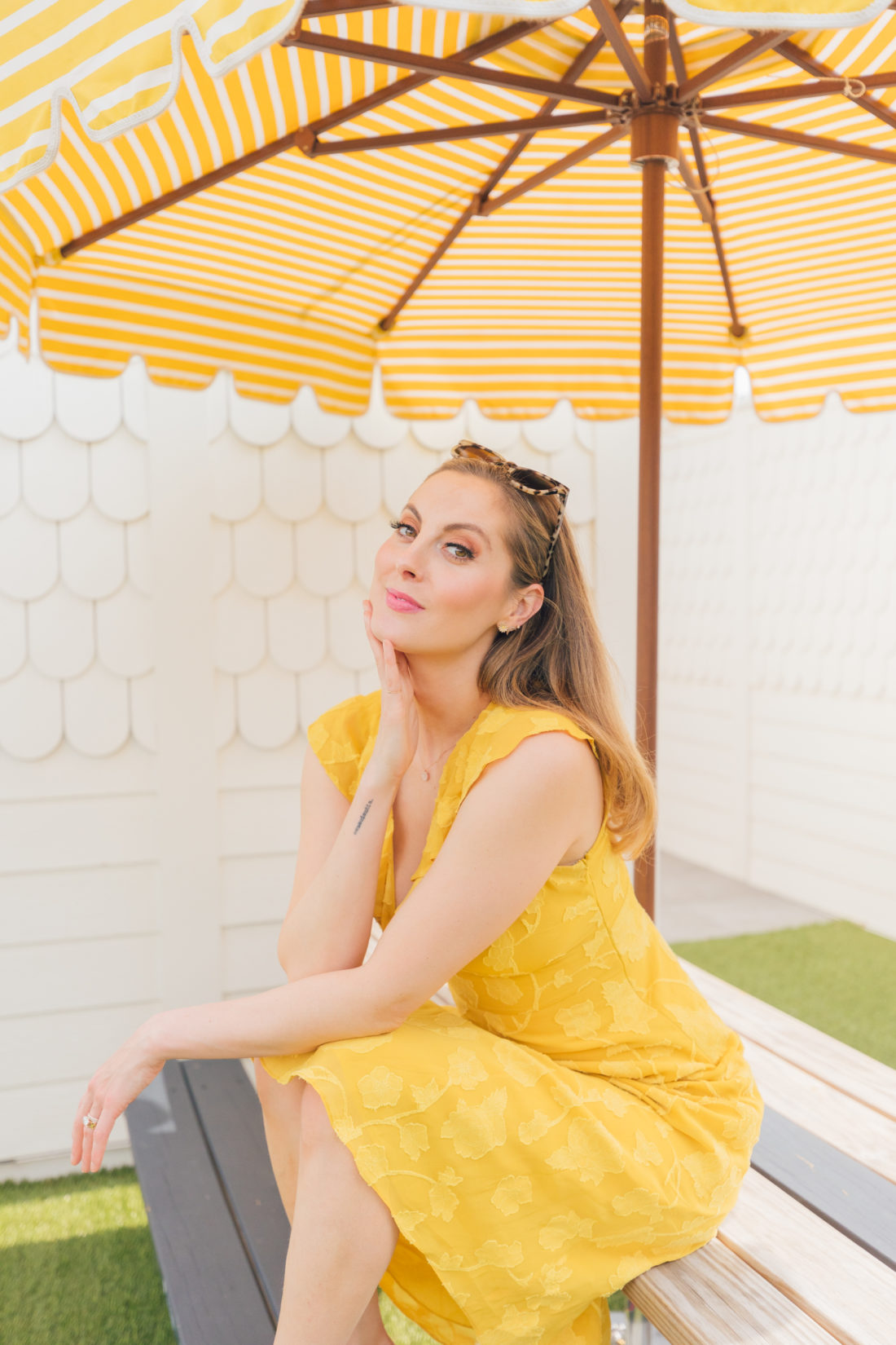 Eva Amurri Martino wears a bright yellow dress next to a yellow striped umbrella