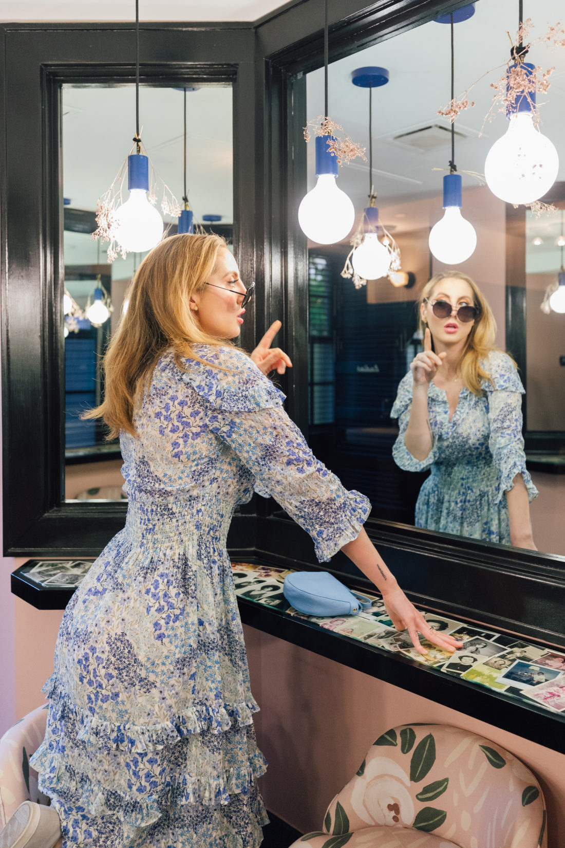 Eva Amurri Martino wears a flowery blue dress and looks in the mirror at the Claremont Hotel in Atlanta