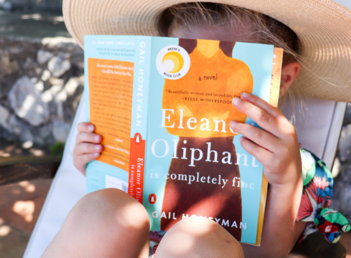 Eva Amurri Martino sits with daughter Marlowe on a chair in Amalfi reading her newest HEA Book Club pick: Eleanor Oliphant Is Completely Fine