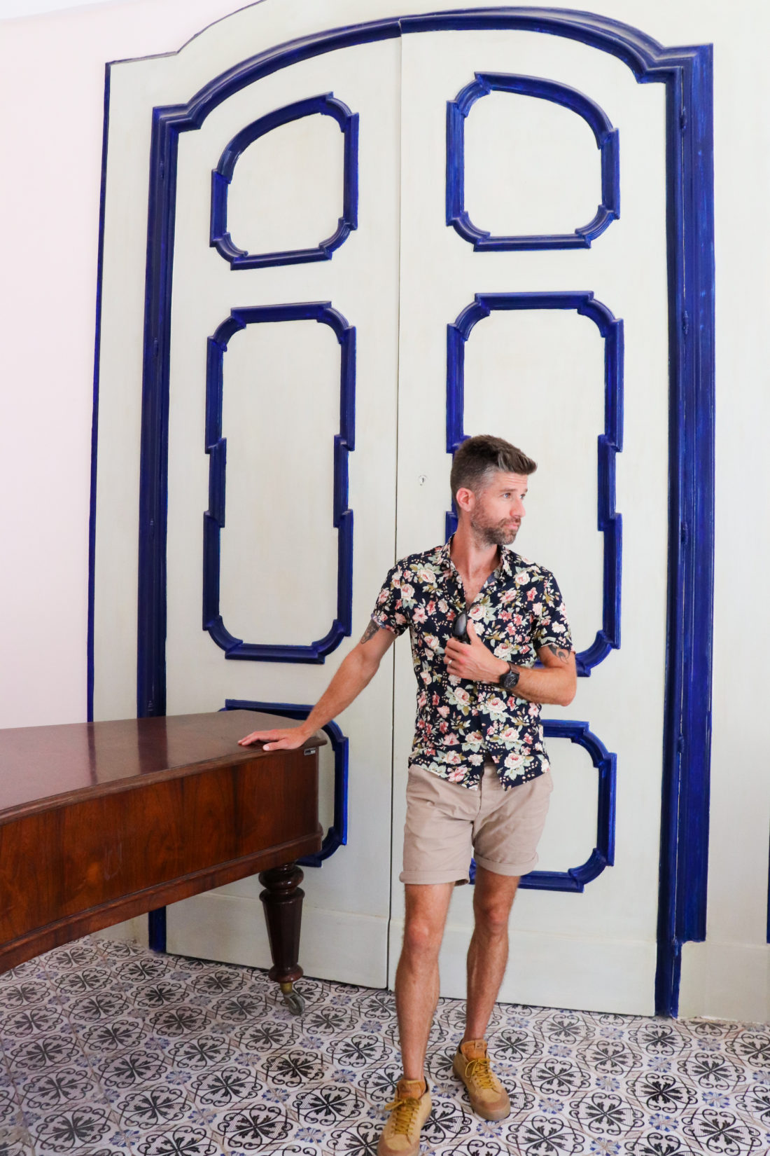 Kyle Martino in front of white and blue doors in Italy