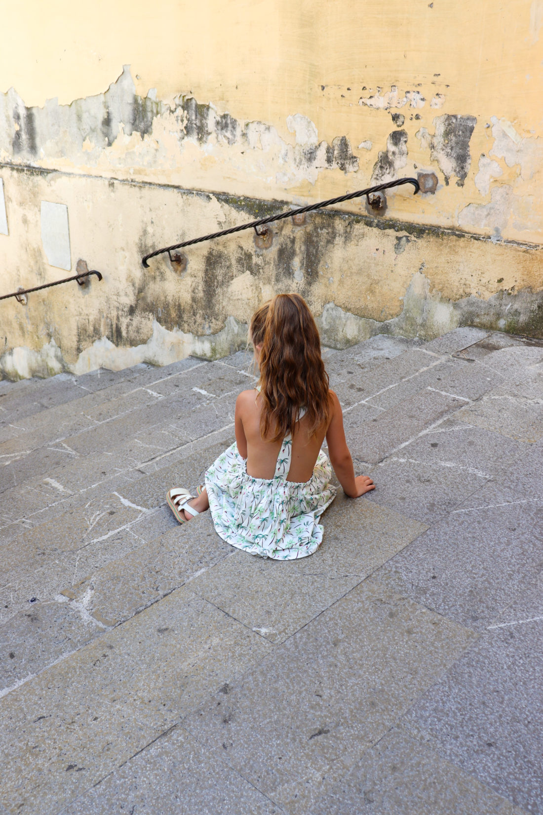 Marlowe Martino sits on the steps on the Amalfi Coast