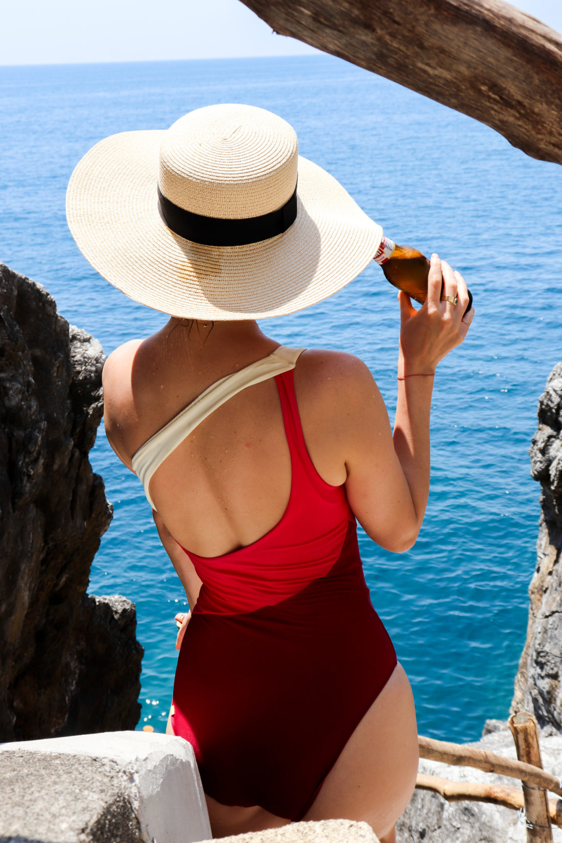Eva Amurri Martino wears a straw hat and bathing suit in the Amalfi Coast