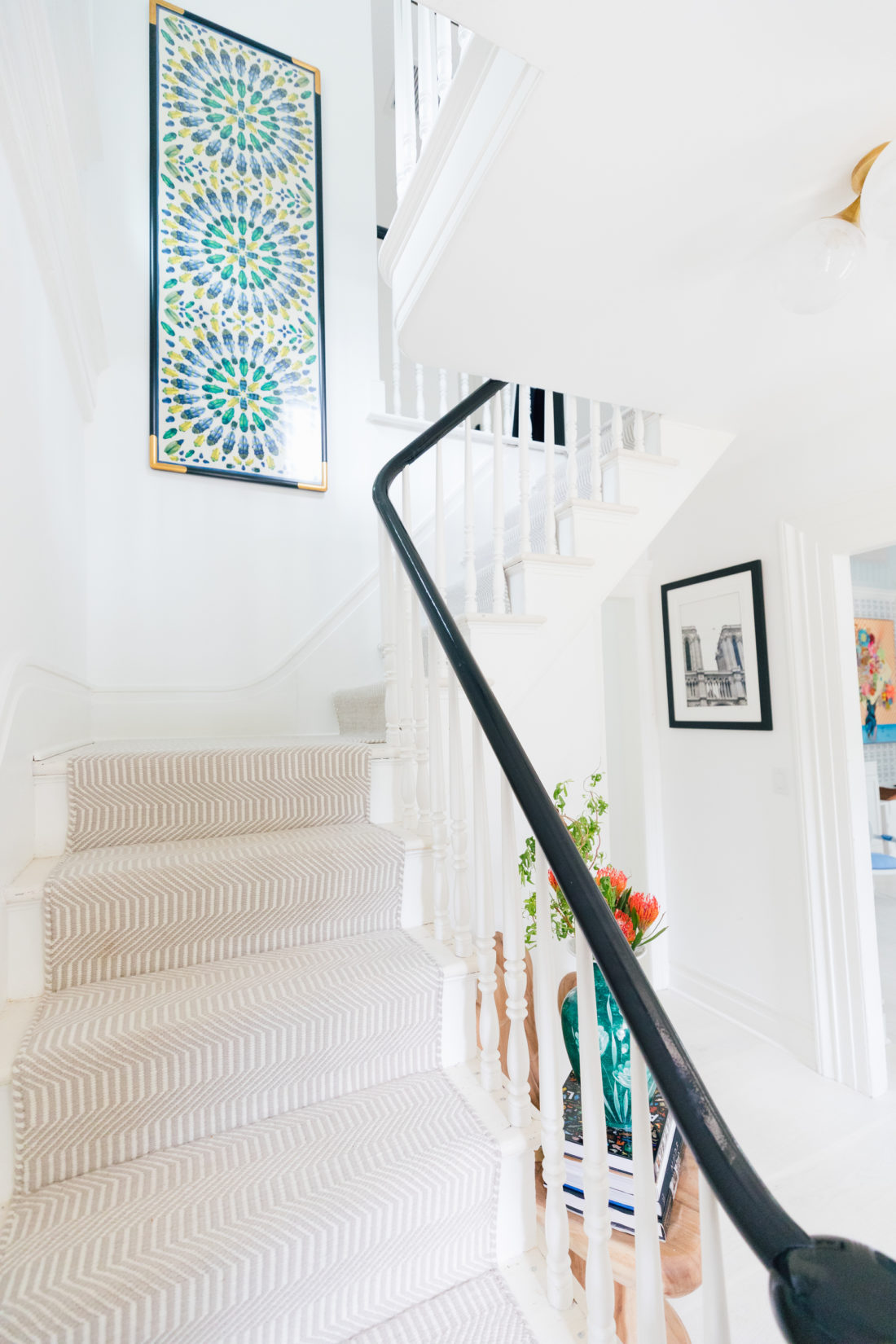 A framed Tory Burch scarf sits atop the stairway in Eva Amurri Martino's entry way