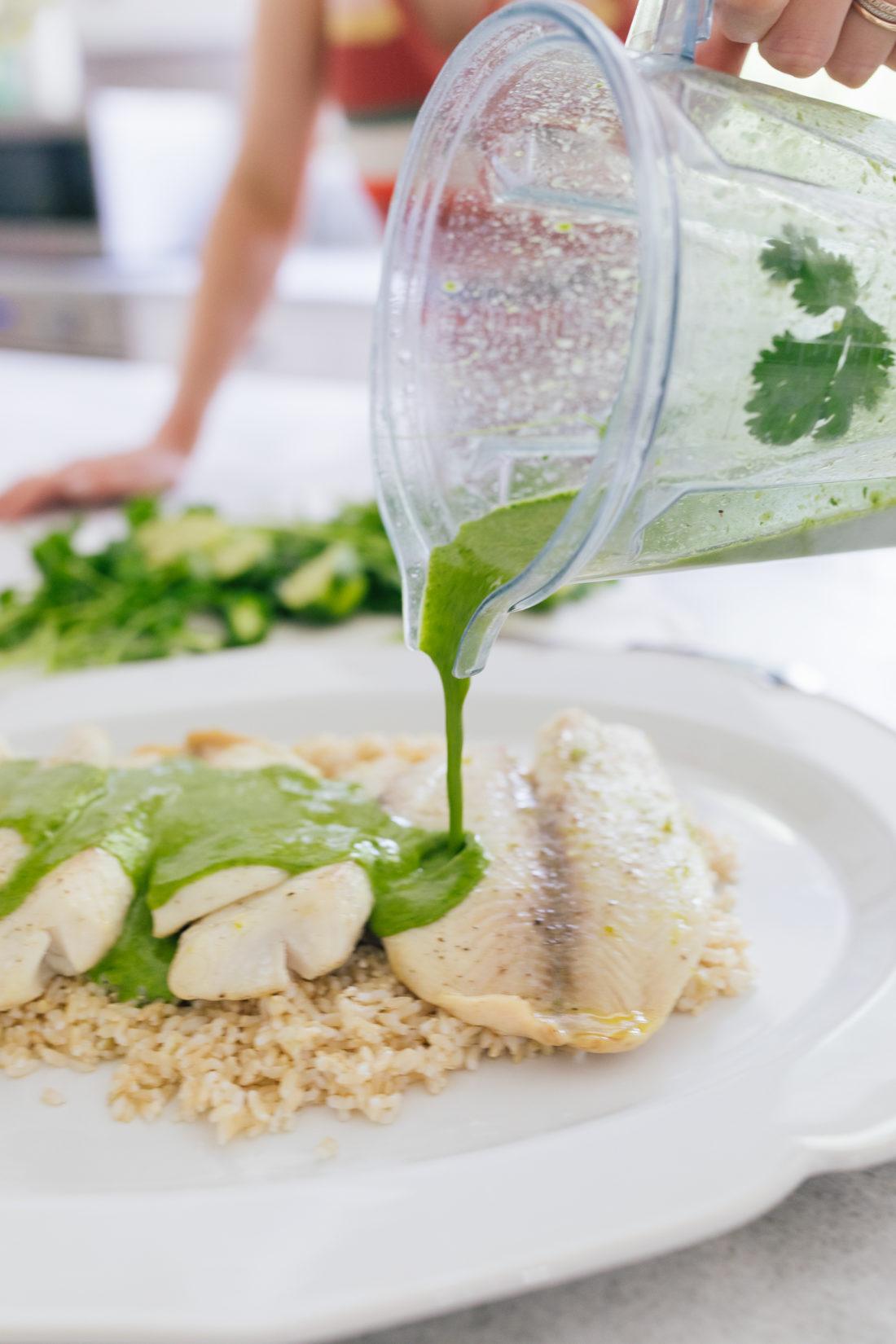 Eva Amurri Martino pours vinaigrette over Tilapia for Buster's Famous Green Fish recipe