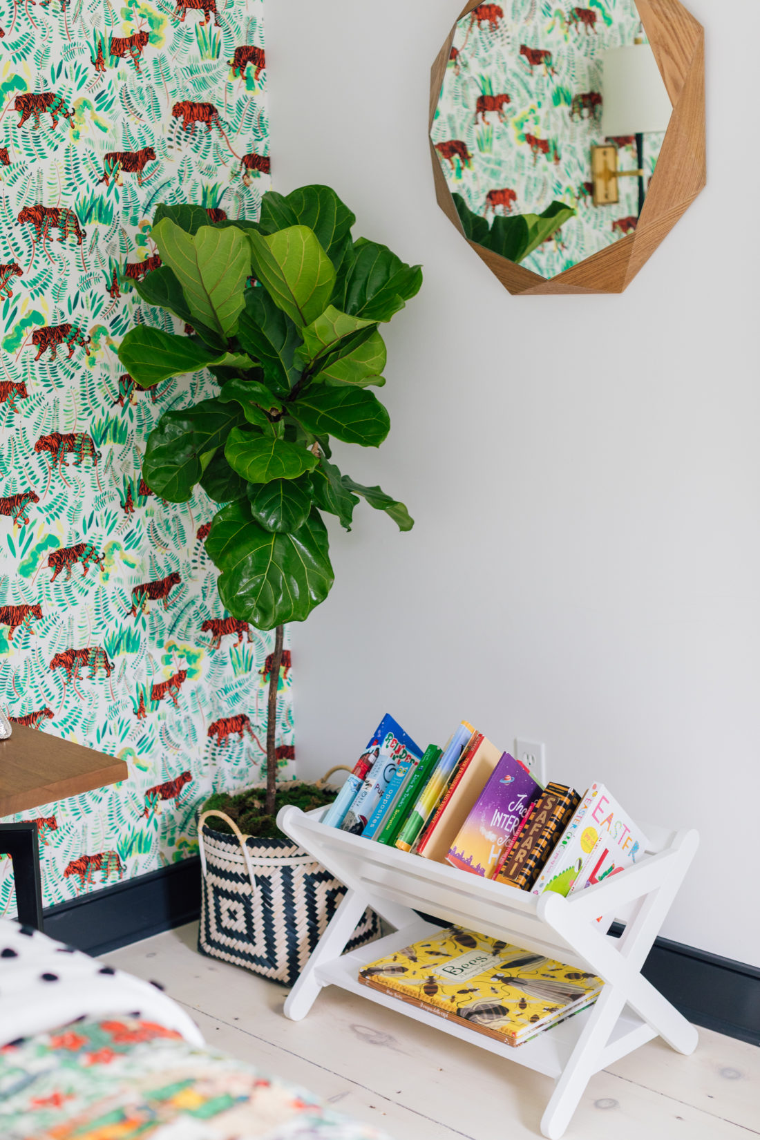 A tree next to colorfully arranged books beneath a mirror in Eva Amurri Martino's son Major's new room.