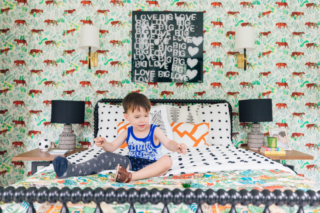 Eva Amurri Martino's son Major sits on his colorful bed in his new bedroom beneath a Kerri Rosenthal print