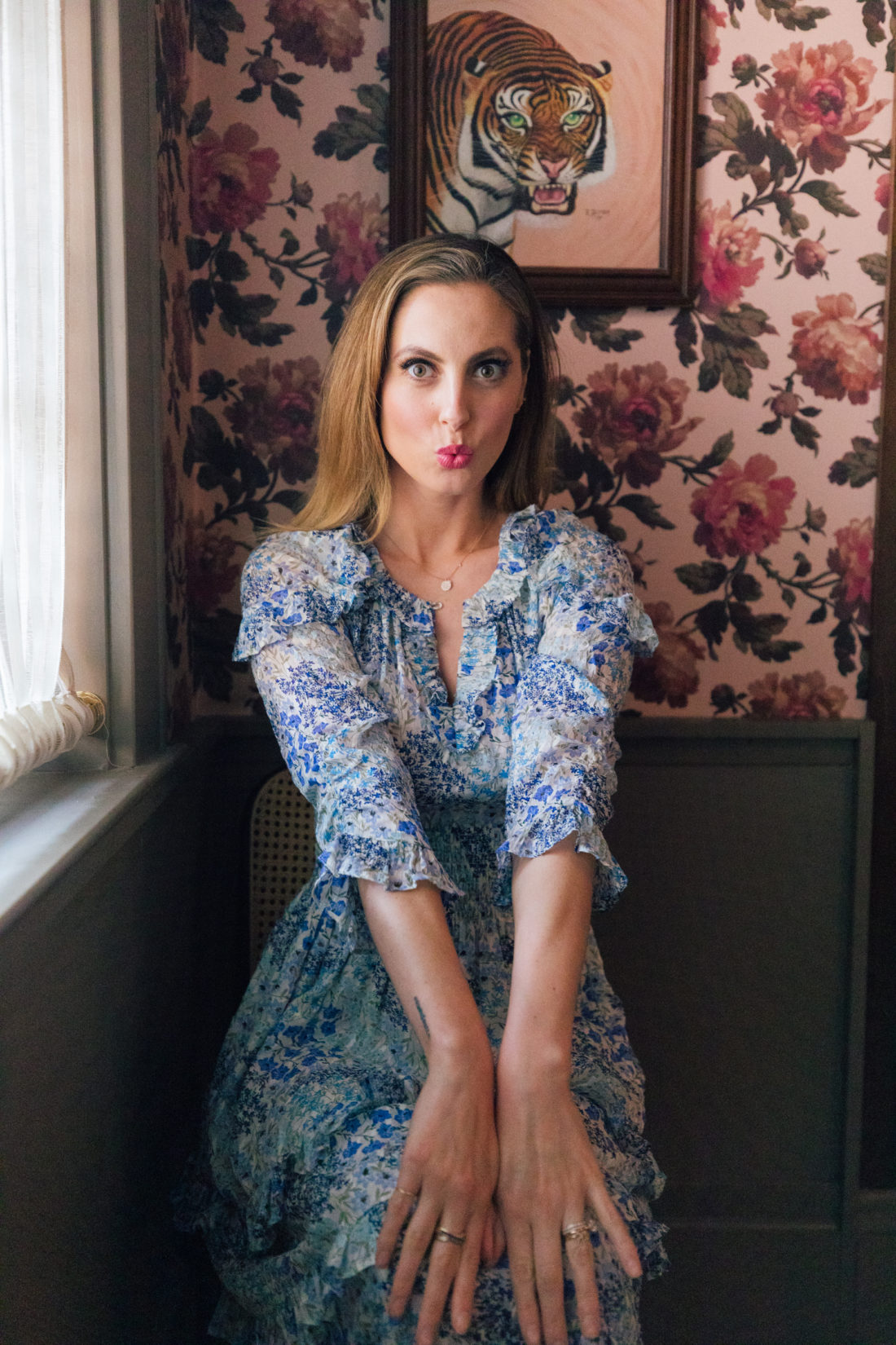 Eva Amurri Martino sits in a floral dress in front of peony wallpaper at the Clermont Hotel