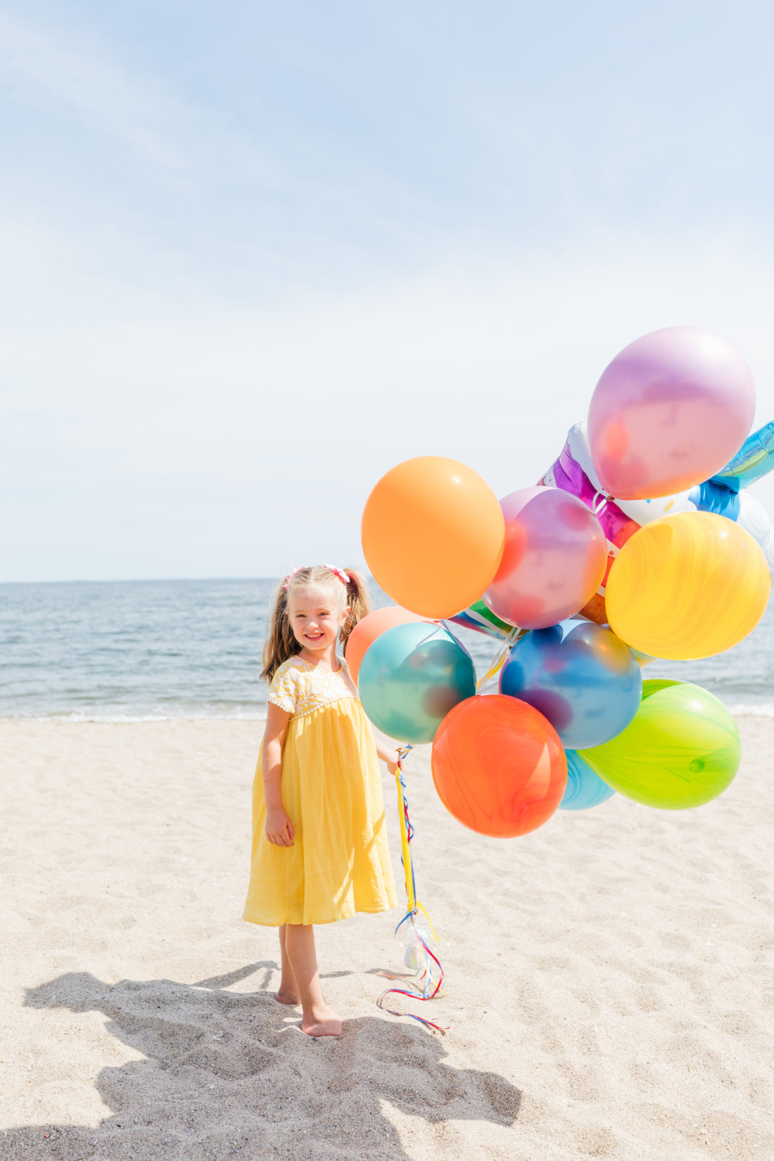 Marlowe Martino holds balloons on the beach in Connecticut to commemorate her 5th birthday
