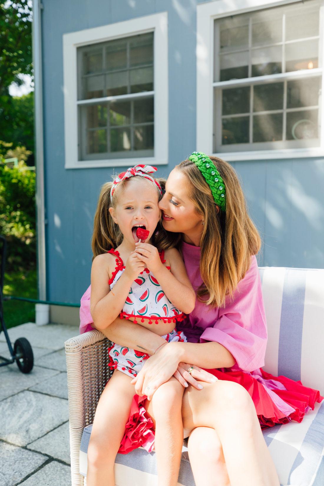 Marlowe Martino sits on mom Eva Amurri Martino's lap eating a watermelon lollipop