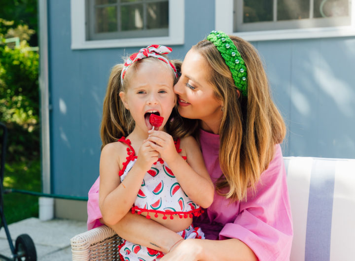Marlowe Martino sits on mom Eva Amurri Martino's lap eating a watermelon lollipop