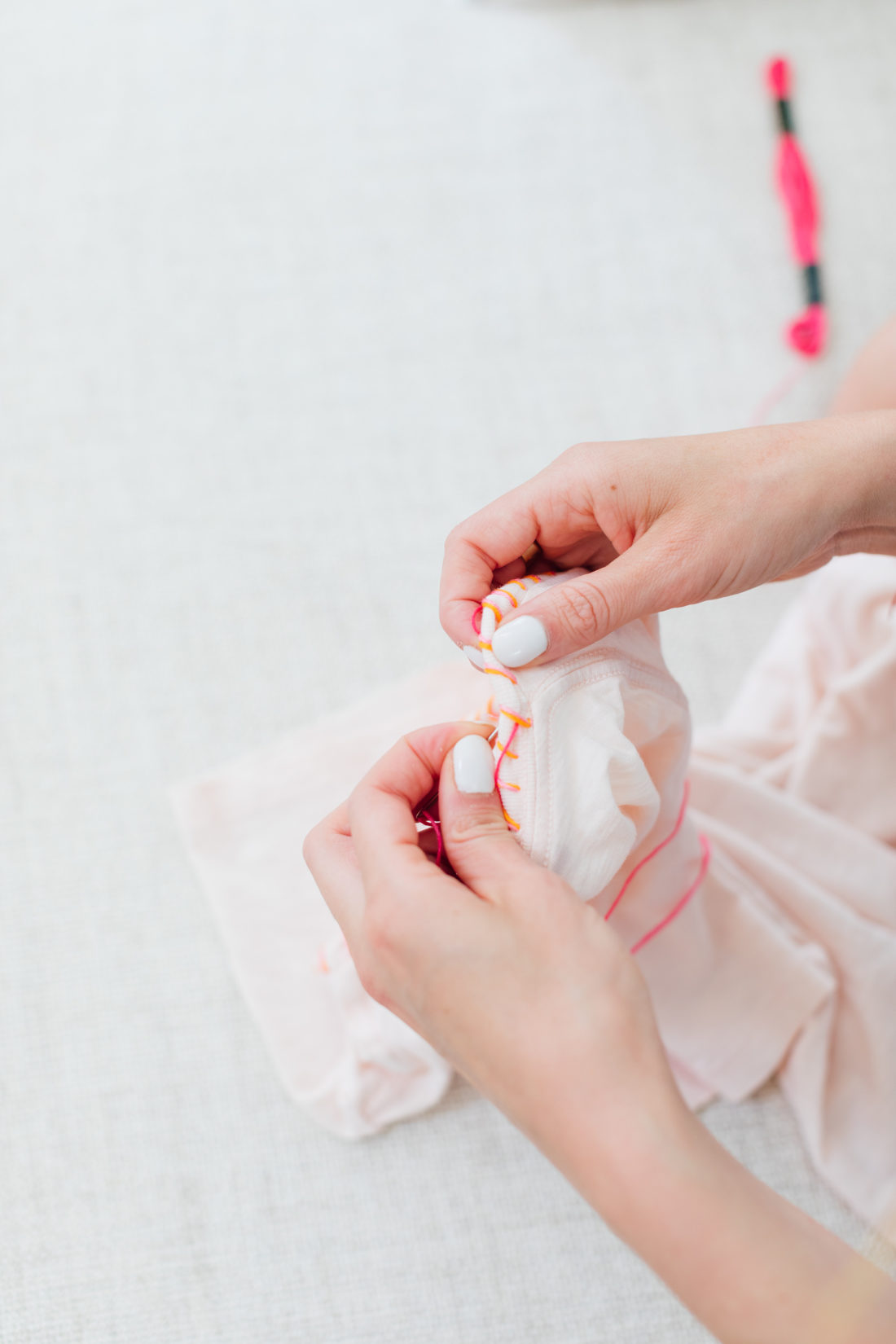 Eva Amurri Martino sewing a detail of thread on the collar of an old tee