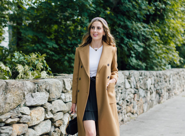 Eva Amurri Martino wears a camel coat, a black skirt and a white top as a neutral color palatte