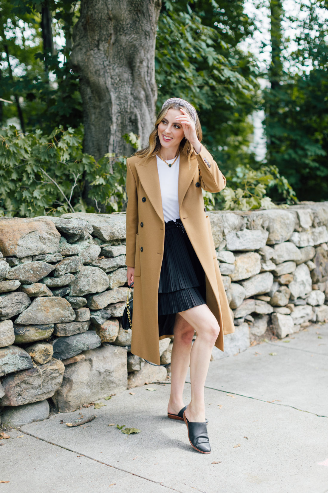 Eva Amurri Martino wears a camel coat, a black skirt and a white top as a neutral color palette