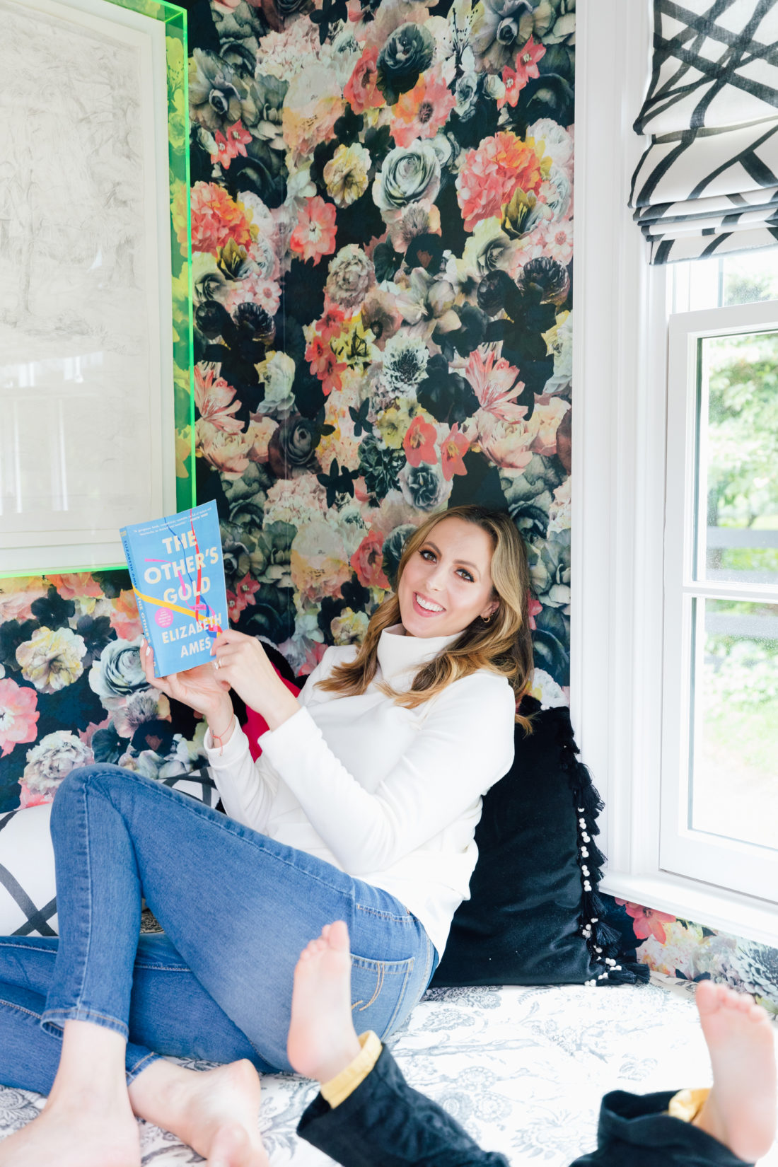 Eva Amurri Martino lies in her snuggle nook reading the 4th HEA Book Club Pick: The Other's Gold by Elizabeth Ames