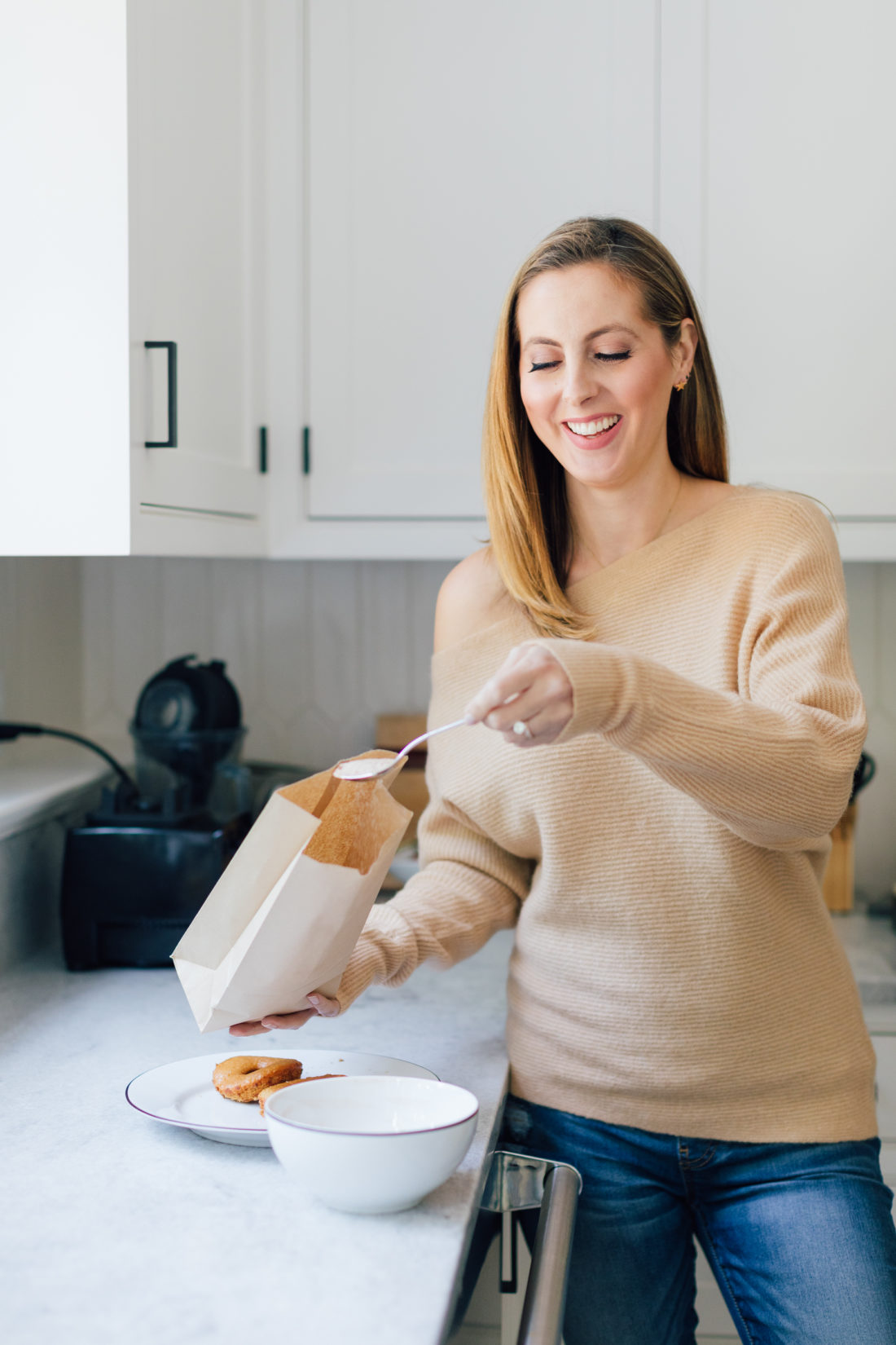 Eva Amurri Martino shakes up her baked apple cider donuts in a brown bag with sugar