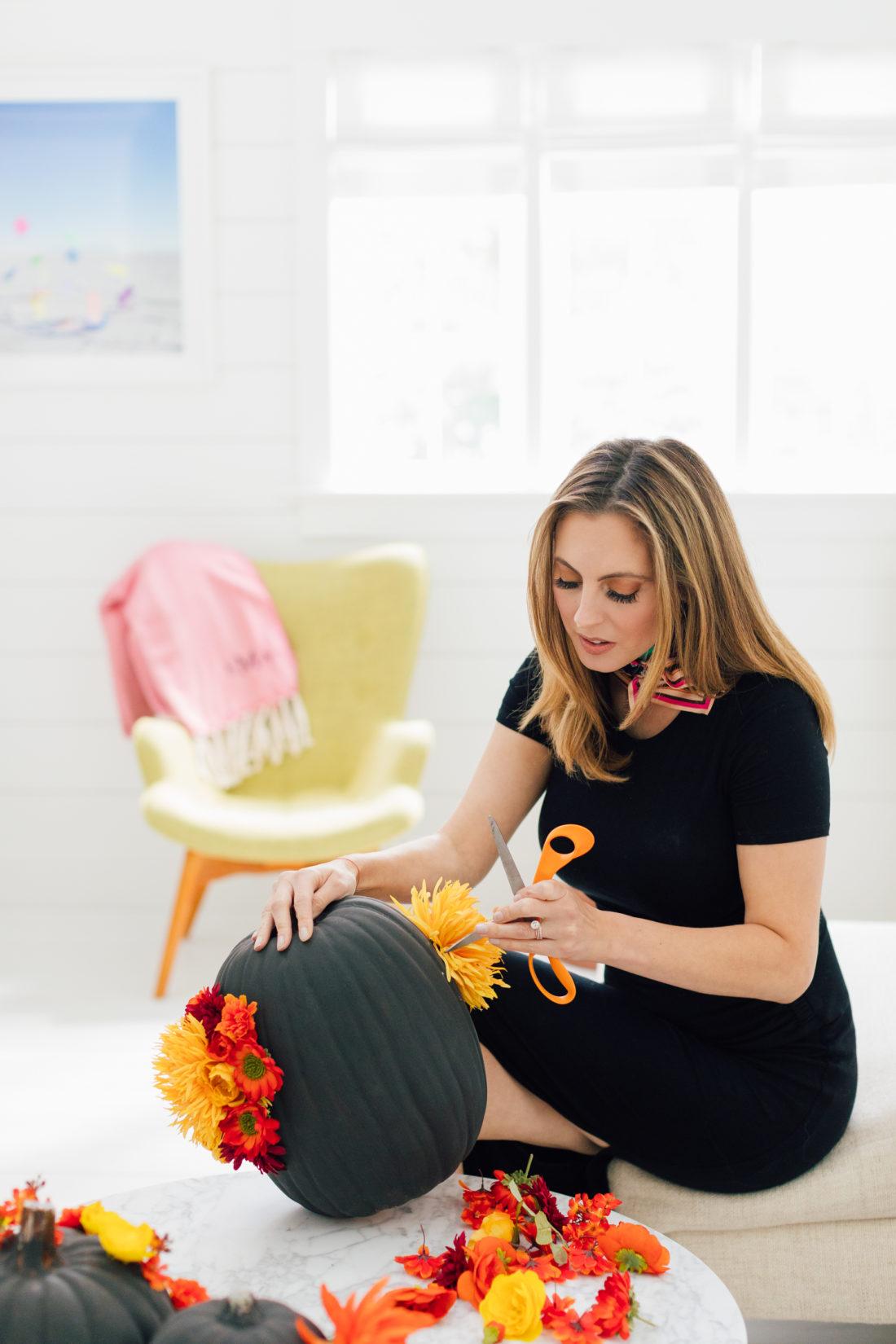 Eva Amurri Martino uses a scissor to make a hole in a craft pumpkin