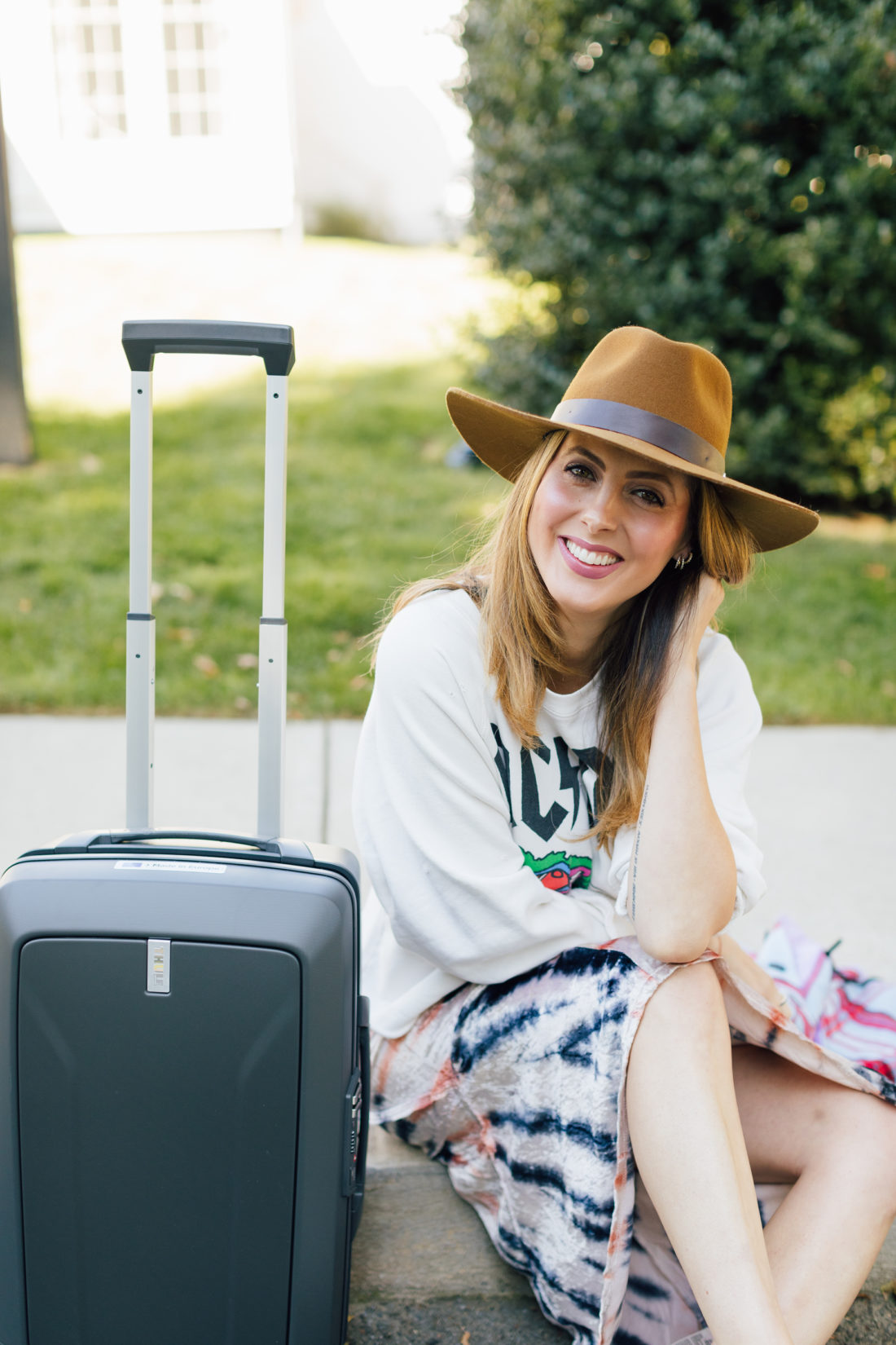 Eva Amurri Martino wears festival chic clothing and poses with Thule luggage outside her connecticut home