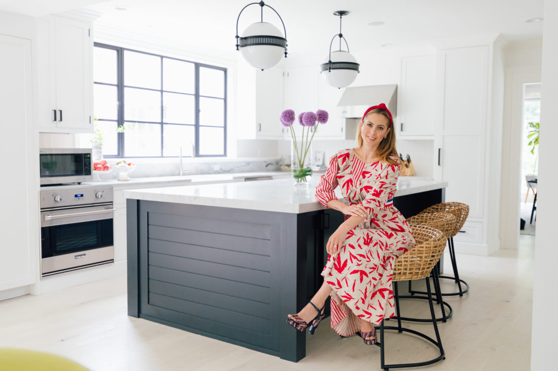 Eva Amurri Martino wears a red and white dress, and sits on a bar stool in the renovated kitchen in her Connecticut home