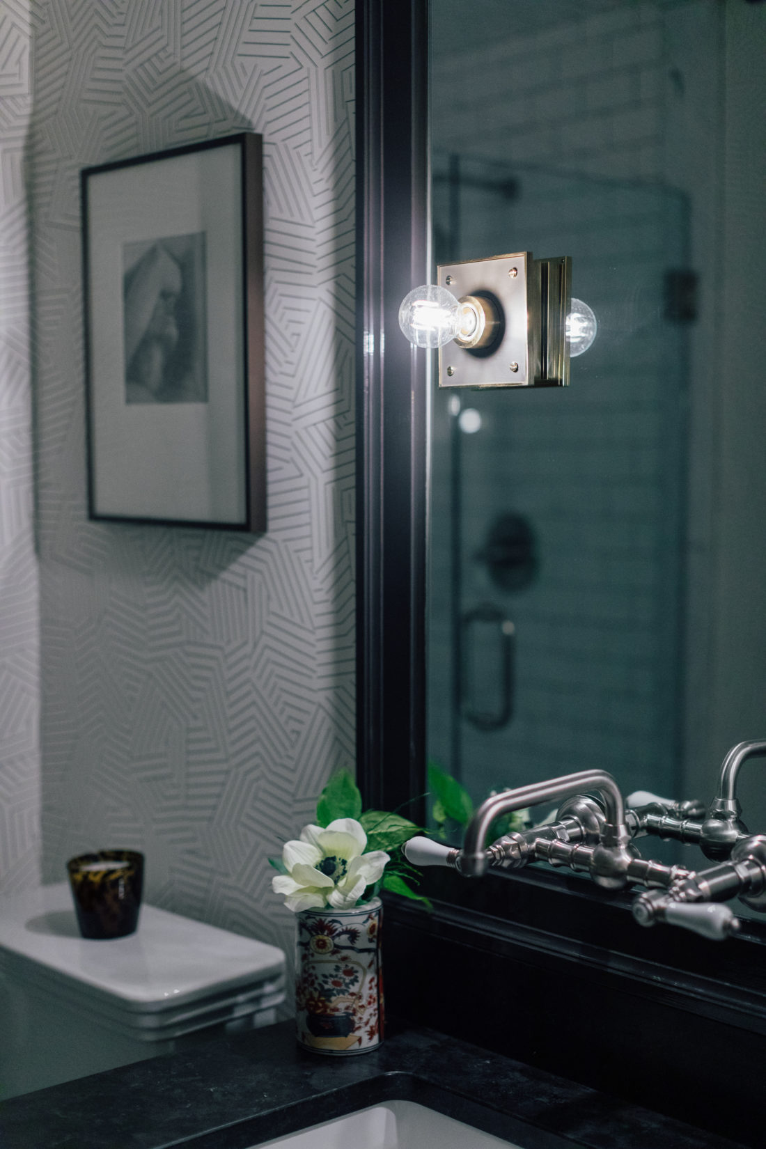 A custom mirror with Urban Electric Pop Sconces that hangs over the Saint Henry Black granite countertop from Polycor inside Kyle Martino's masculine bathroom in his newly renovated Connecticut home