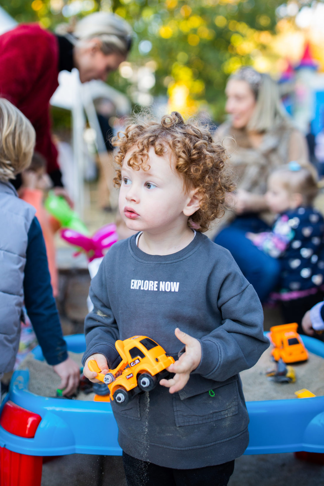 A partygoer playing with a construction truck toy at Major Martino's Construction Zone themed birthday party