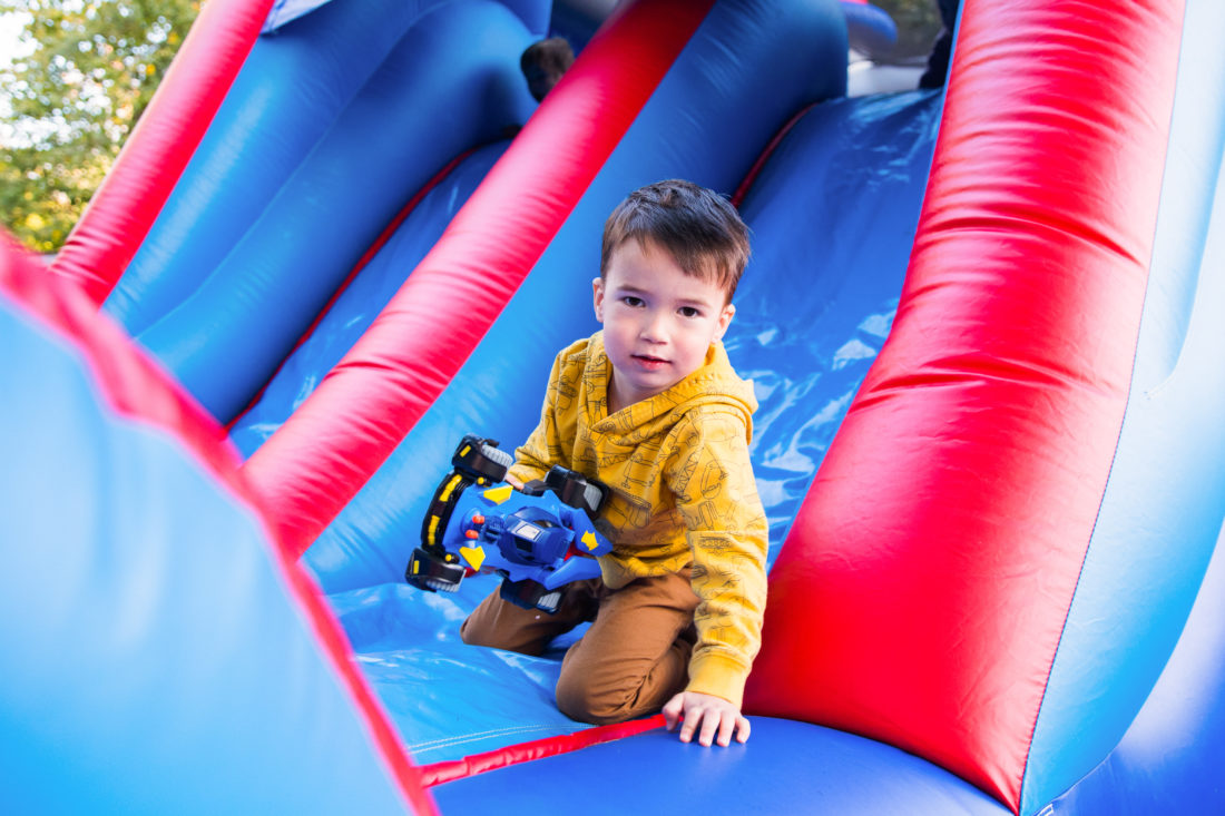 Major Martino slides down the side of the Bounce House at his Construction Zone themed birthday party