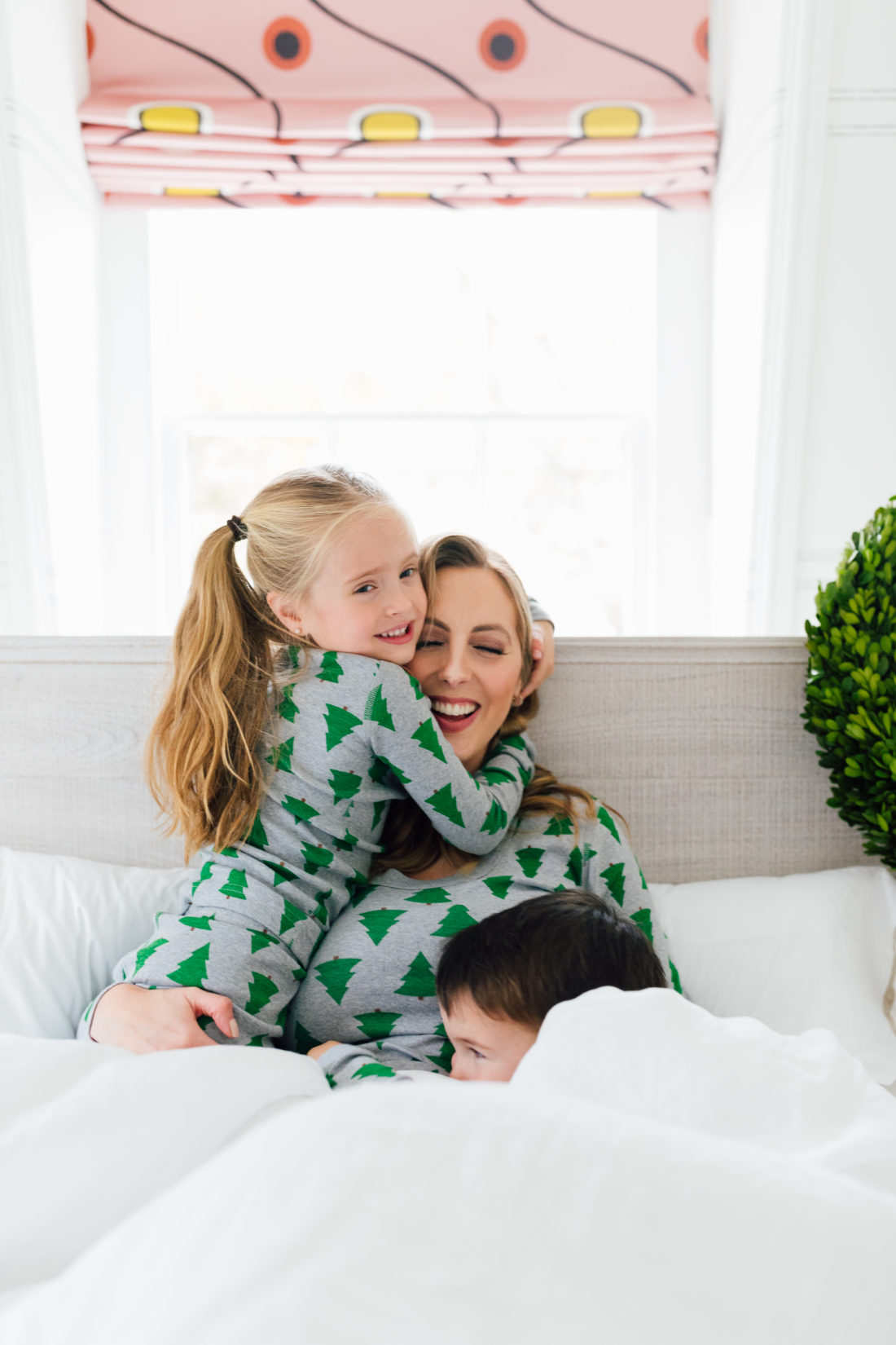 Eva Amurri Martino cuddles with her kids in bed wearing matching holiday pajamas