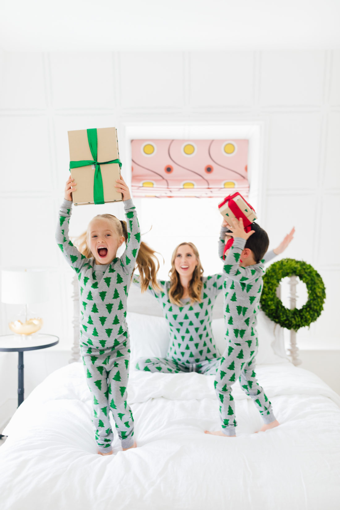 Eva Amurri Martino and her kids Marlowe and Major wear matching holiday pajamas and hold wrapped gifts in bed