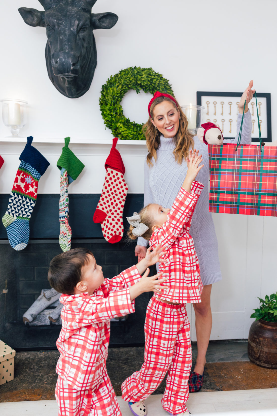 Eva Amurri Martino tempts children Marlowe and Major with a wrapped gift, in their matching pajamas, standing in front of their Christmas stockings, all from Garnet Hill