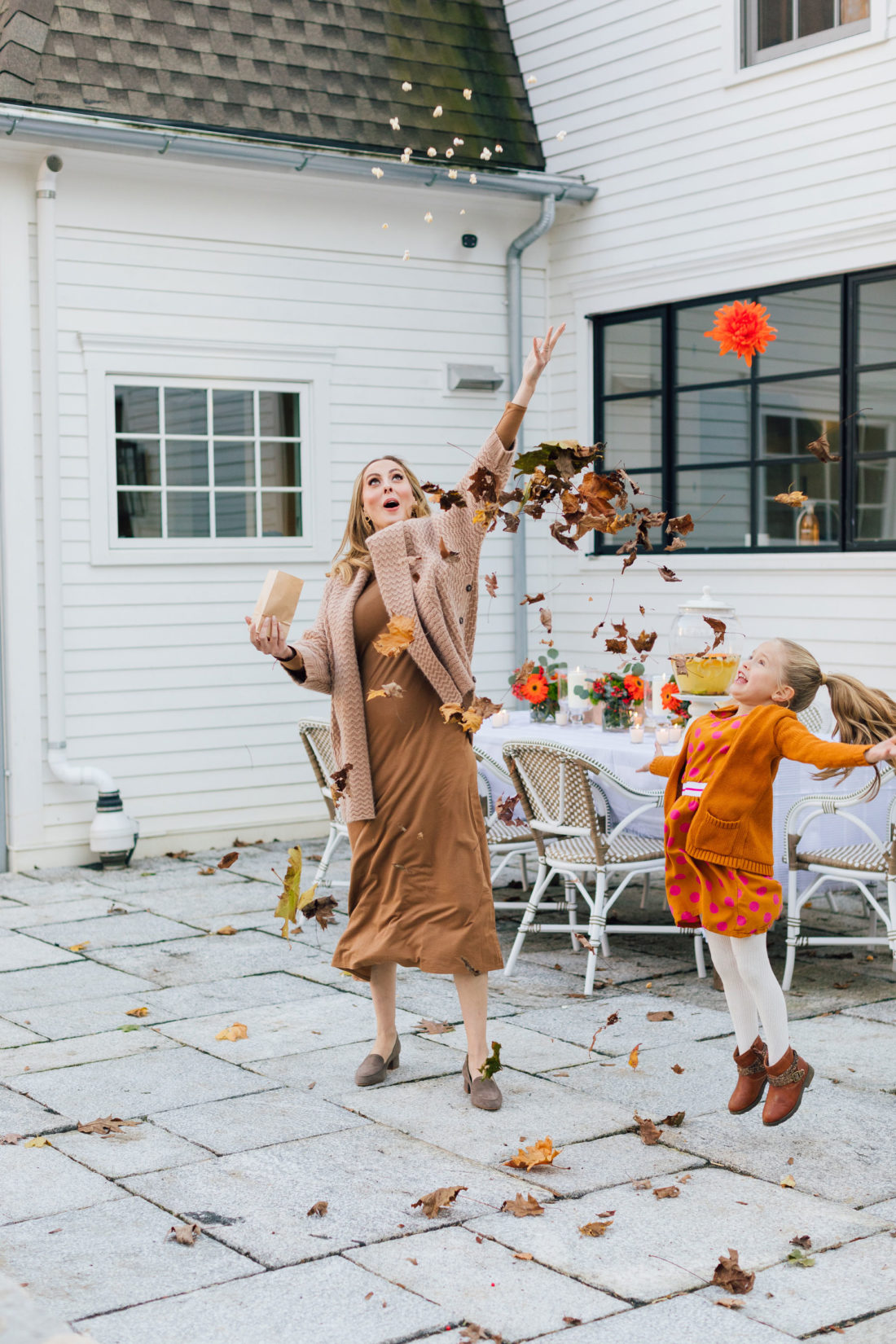 Eva Amurri and daughter Marlowe throw a pile of leaves in the air before an outdoor movie night on the back patio of her Connecticut home
