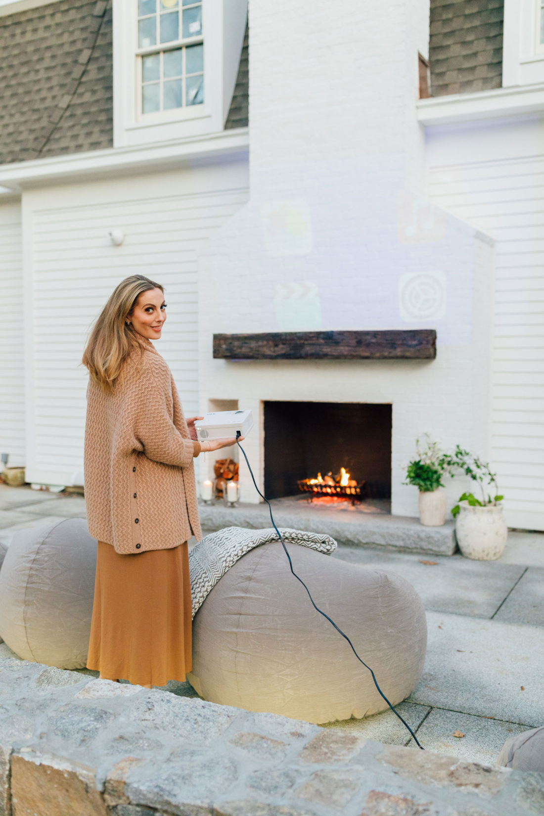 Eva Amurri holds a portable projector for an outdoor movie night on her back patio at her home in Connecticut