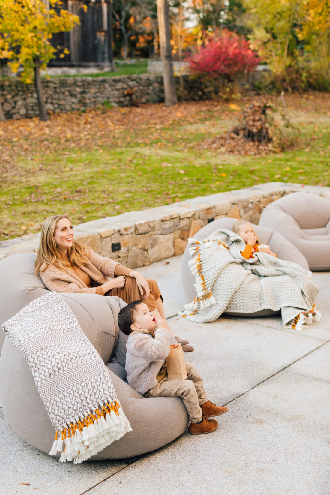 Eva Amurri and kids Marlowe and Major sit on beanbag chairs for an outdoor movie night on the back patio of her Connecticut home