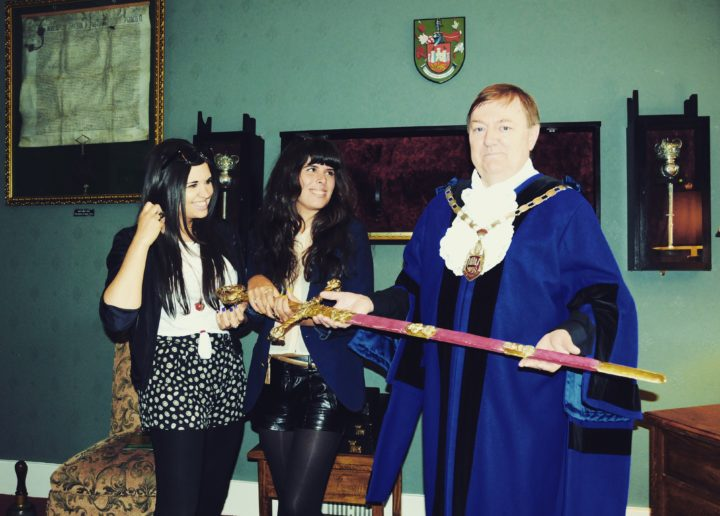 Eden Cale holds Henry VII's sword with visual artist Swci Delic and the Sheriff of Carmarthen Alun Lenny
